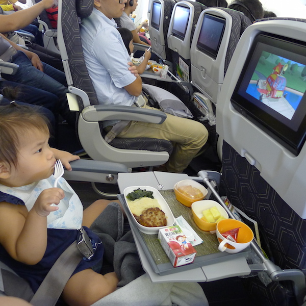 Child enjoys meal on plane